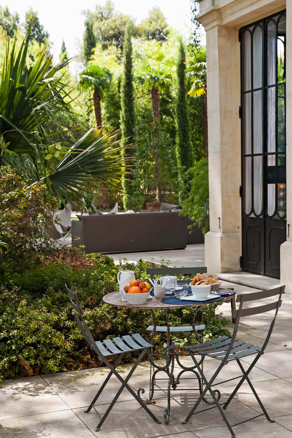 Bistro set in a peaceful Avignon garden. Come see a Breathtaking French Château Tour in Provence With Photo Gallery of Historical Architecture, Dramatic Eclectic Interiors & Oddities!