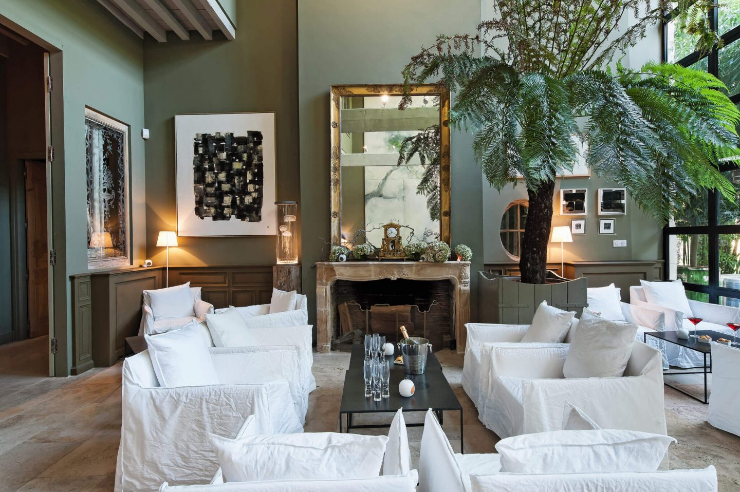 White slipcovered modern arm chairs in a deep green painted salon. Serene French Country Style interior design inspiration. The Serenity Suite at Avignon Hôtel Particulier. Luxurious and timeless restored 19th century French chateau in the South of France. Provencal romance, traditional architecture, modern French design, unique art, and European antiques. Photo: Haven In.