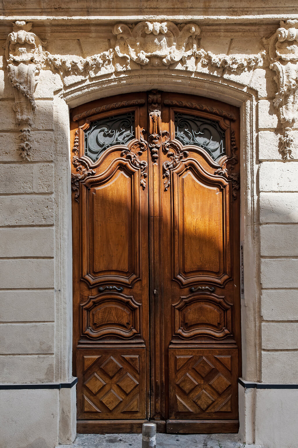Magnificent antique French wood doors and limestone facade. Photo: Haven In.
