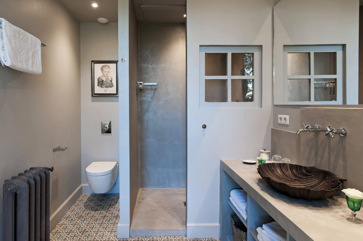Interior window in a walk-in shower to maximize natural light in a serene, modern, spare bathroom. Serene French Country Style interior design inspiration. The Serenity Suite at Avignon Hôtel Particulier. Luxurious and timeless restored 19th century French chateau in the South of France. Provencal romance, traditional architecture, modern French design, unique art, and European antiques. Photo: Haven In.
