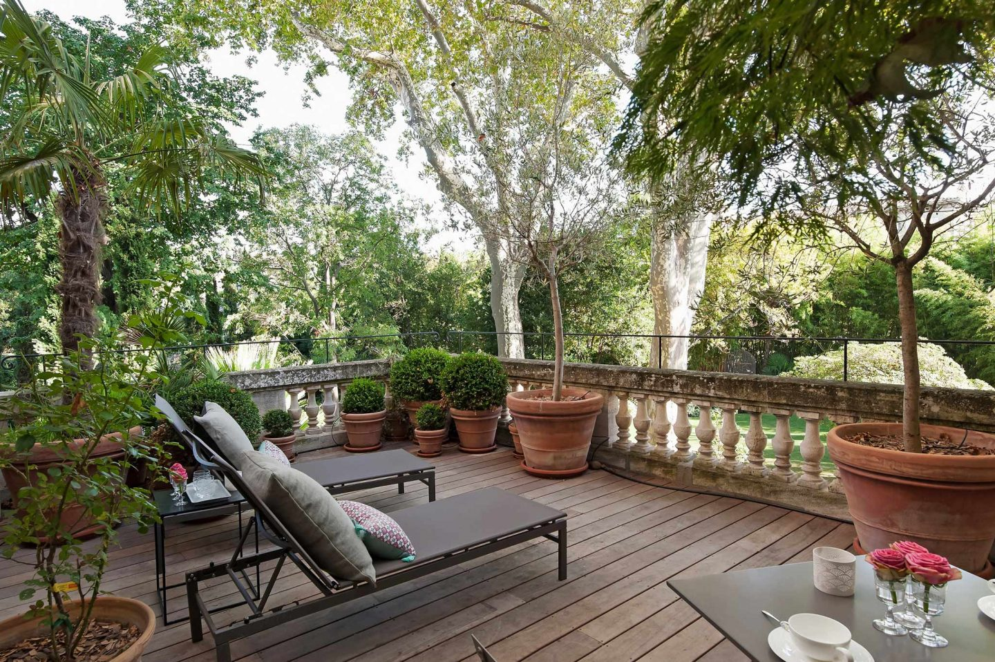 Terrace overlooking a lush garden in Avignon. Serene French Country Style interior design inspiration. The Serenity Suite at Avignon Hôtel Particulier. Luxurious and timeless restored 19th century French chateau in the South of France. Provencal romance, traditional architecture, modern French design, unique art, and European antiques. Photo: Haven In.