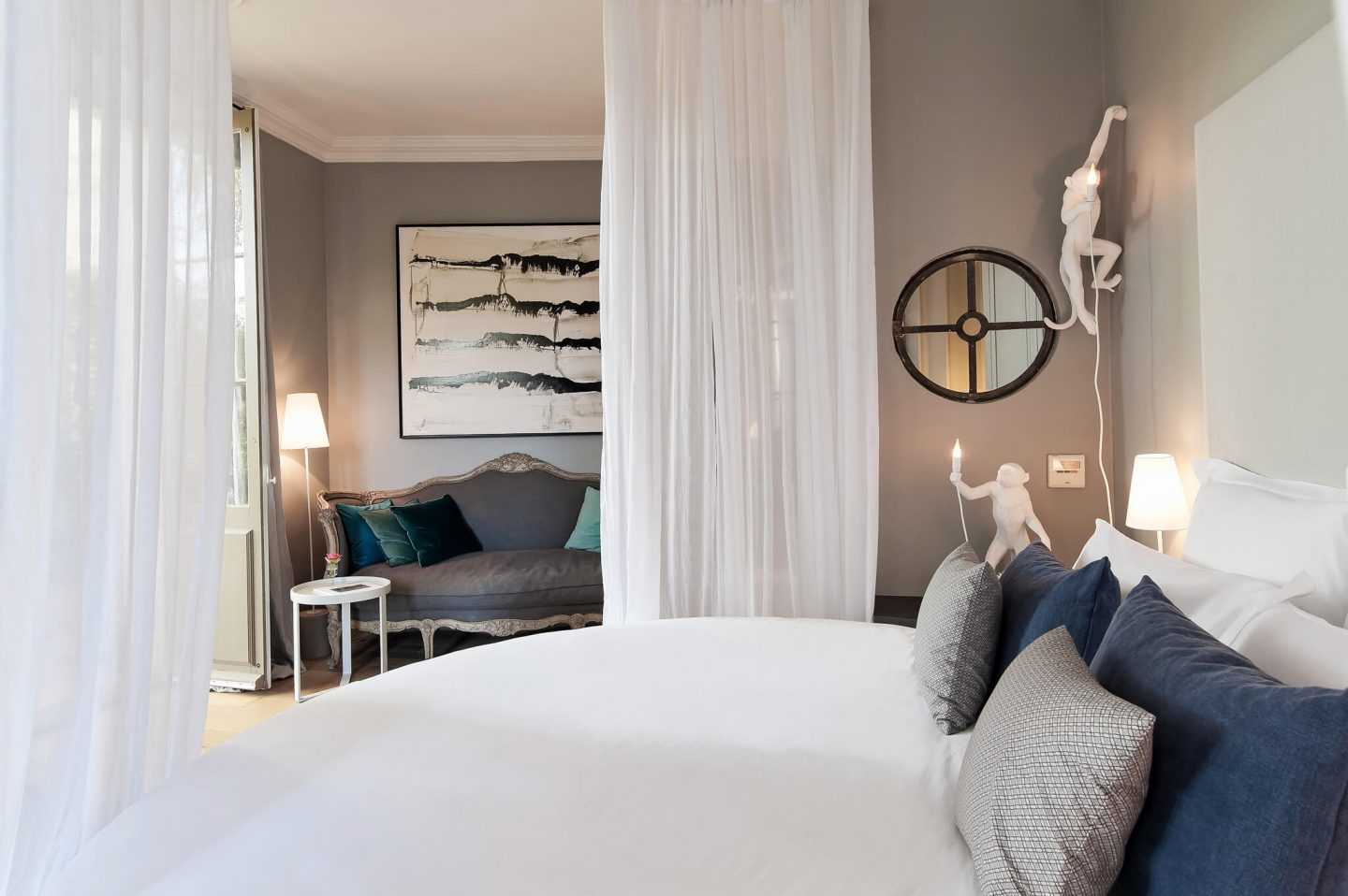Grey walls, monkey art, and billowy white sheer curtains decorate the suite's bedroom. Serene French Country Style interior design inspiration. The Serenity Suite at Avignon Hôtel Particulier. Luxurious and timeless restored 19th century French chateau in the South of France. Provencal romance, traditional architecture, modern French design, unique art, and European antiques. Photo: Haven In.