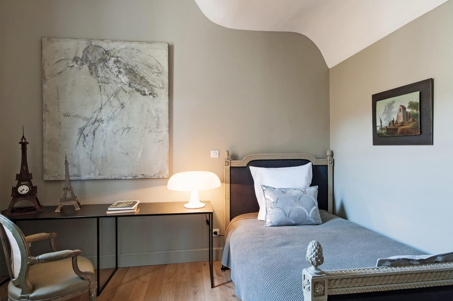 Modern art and a traditional style French country bed join a modern desk in a bedroom suite. Serene French Country Style interior design inspiration. The Serenity Suite at Avignon Hôtel Particulier. Luxurious and timeless restored 19th century French chateau in the South of France. Provencal romance, traditional architecture, modern French design, unique art, and European antiques. Photo: Haven In.