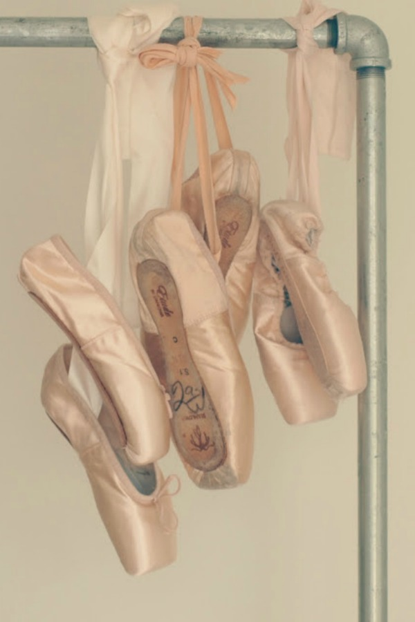 Pink ballet slippers (pointe shoes) hung from an industrial garment rack by Hello Lovely Studio. #balletslippers #ballerina #pointeshoes #hellolovelystudio #romanticdecor #shabbychic