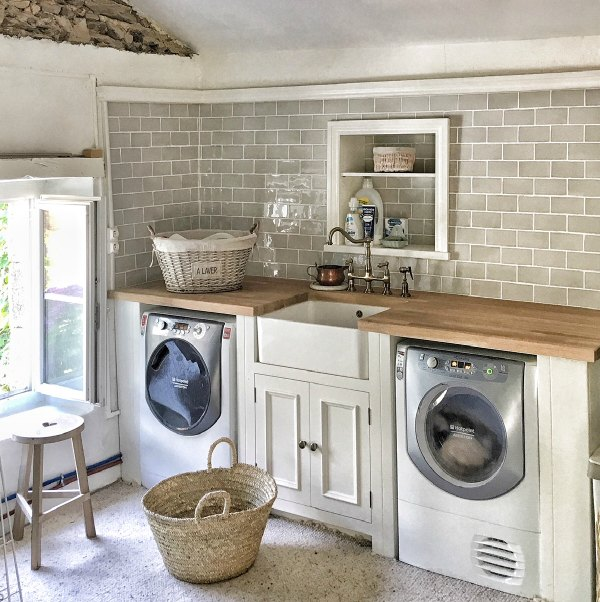 Charming French farmhouse laundry room by Vivi et Margot with farm sink, French laundry basket, tiled wall, and breezy European country style.