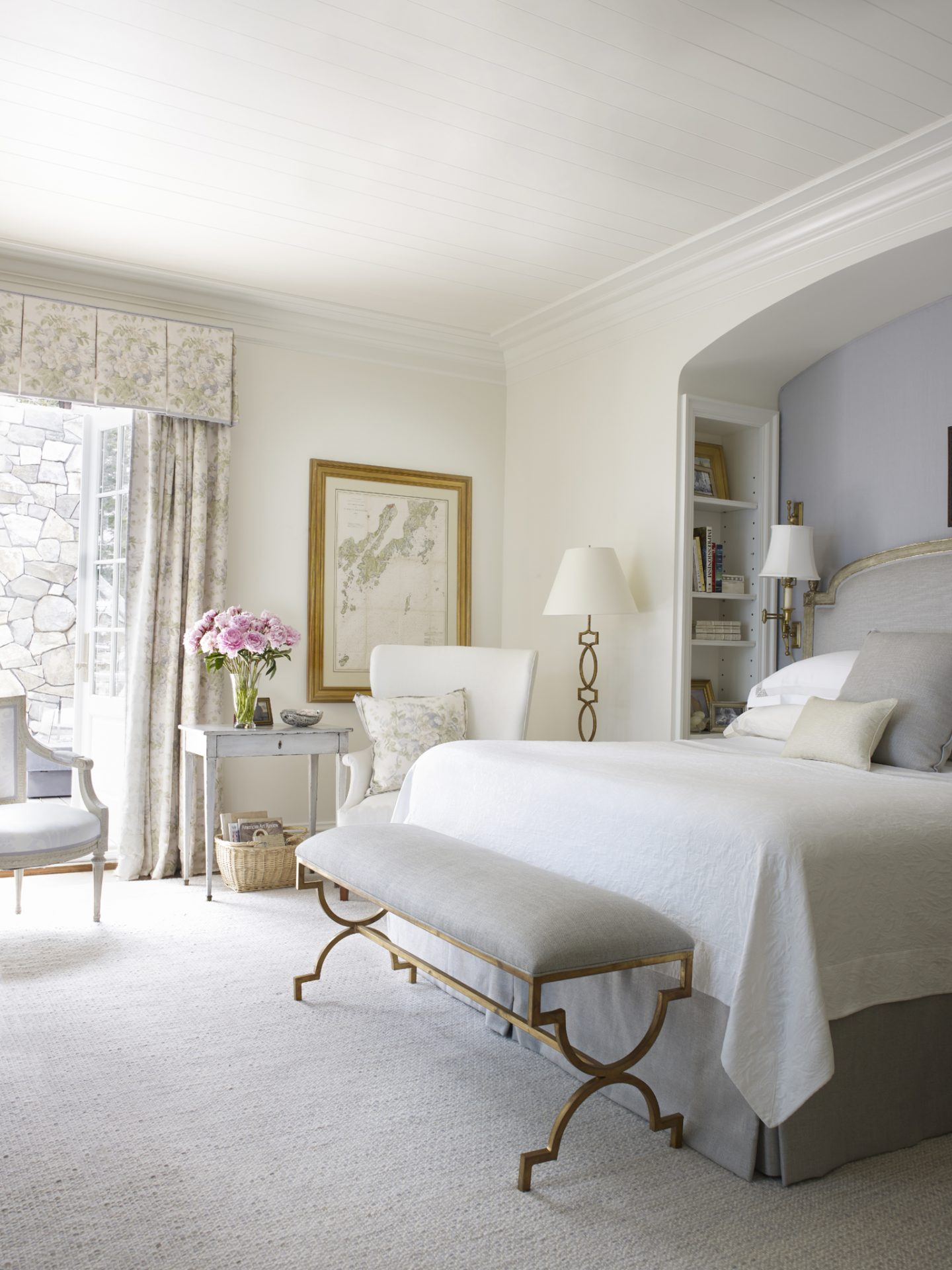 In an architecturally magnificent home in Maine with interior design by Suzanne Kasler, the master bedroom is bright and full of light. The tranquil pale blue grey accents and soothing sumptuous fabrics set a peaceful tone in the heavenly retreat.