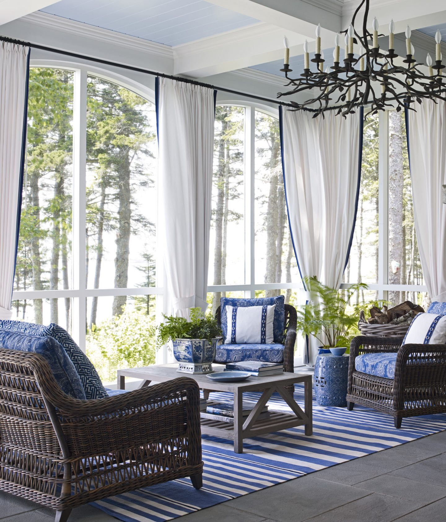 In an architecturally magnificent home in Maine with interior design by Suzanne Kasler, the enclosed porch is attached to the main house. Linen curtains give the exterior room the feeling of an interior room. Bold blue and white stripe rug, various printed fabrics on rattan chair cushions, and blue garden stools are classic coastal design elements offering a warm welcome with cool tones.