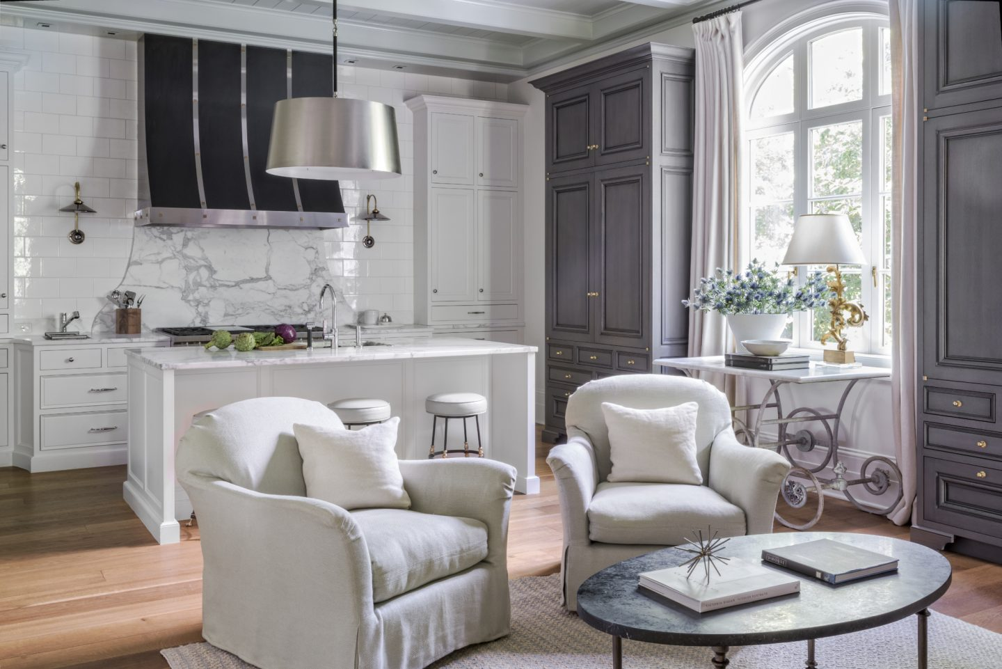 A tailored white kitchen with design by Suzanne Kasler. White walls and weathered grayarmoires. Custom black hood with metallic detail over range. The French pastry table was found at 1stdibs. Belgian chairs in rustic linen. #suzannekasler #kitchen #sophisticateddecor #elegantdecor #interiordesign