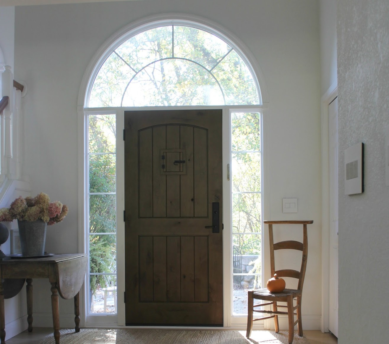 Entry with rustic alder door, French prayer chair, and simple serene fall decor. Hello Lovely Studio.#hellolovelystudio #entry #frontdoor