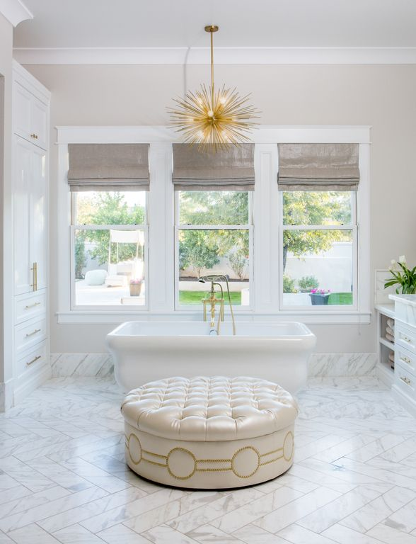 Tufted ottoman and luxurious freestanding tub in marble bathroom. Modern Chic Home in the Southwest. E&A Builders. Pinnacle Conceptions. Jaimee Rose Interiors. #modern #French #housedesign #luxuryhome