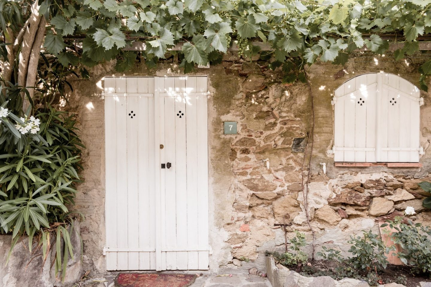 French farmhouse with stone, lush greenery, and white doors. Photo: The Flying Dutchwoman. #frenchfarmhouse #rustic #stone #oldworld #vintagedoors