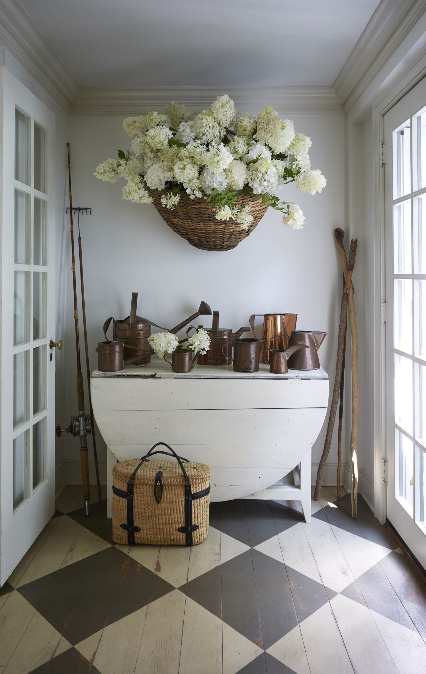 Nora Murphy country house entry with checkerboard pattern flooring, dropleaf table, and huge basket of hydrangea and collection of watering cans. Nora Murphy Country Style to Inspire! #noramuphy #countrystyle #entry #countryhouse #americanfarmhouse #farmhousestyle #rusticdecor