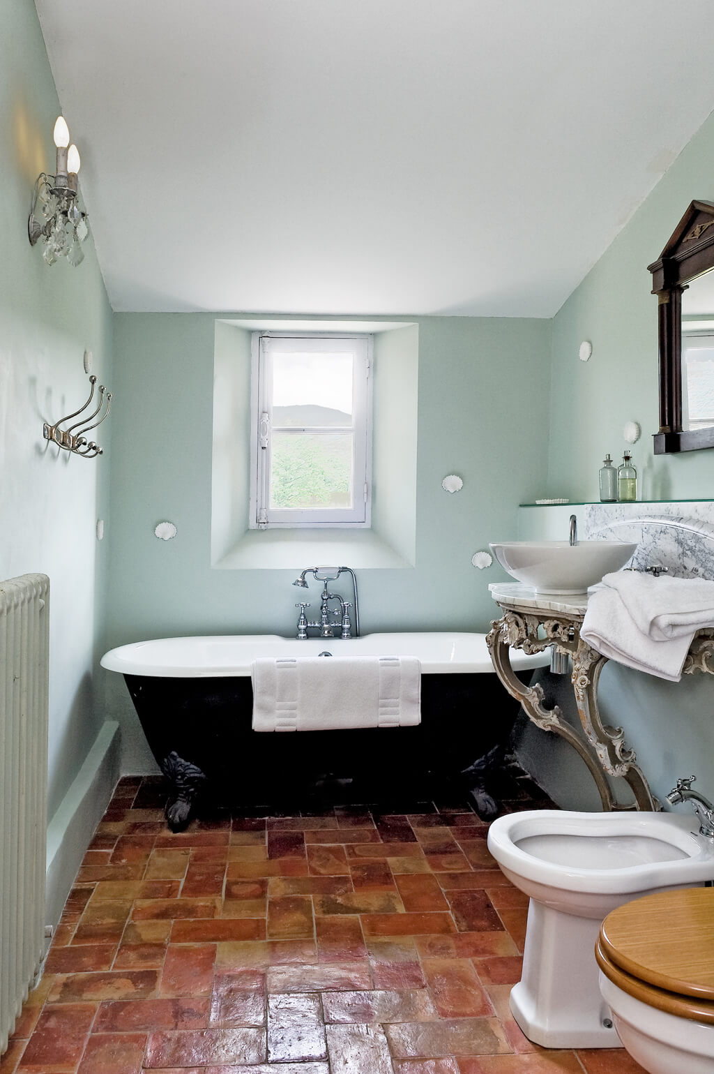 Vintage style bathroom in a French farmhouse with terracotta tile floor.