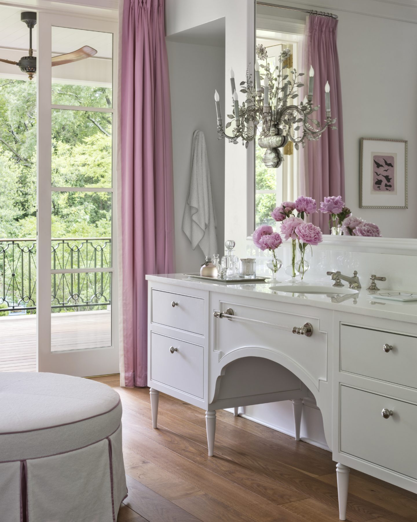 Exquisite and luxurious white bathroom design by Suzanne Kasler with vintage sideboard style vanity and cheerful pink accents.