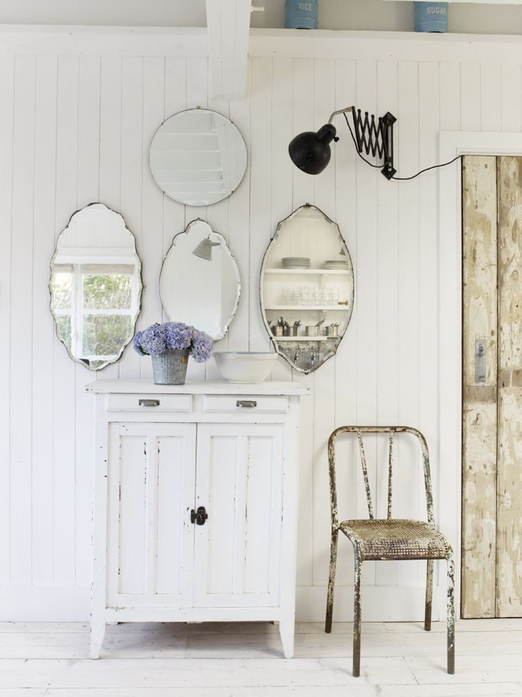 A gorgeous shabby chic vignette with vintage mirrors massed over a country painted cabinet. The Beach Studios. Atlanta Bartlett & Dave Coote. #shabbychic #interiordesign #vintagestyle #whitecottage #mirrors #romanticdecor
