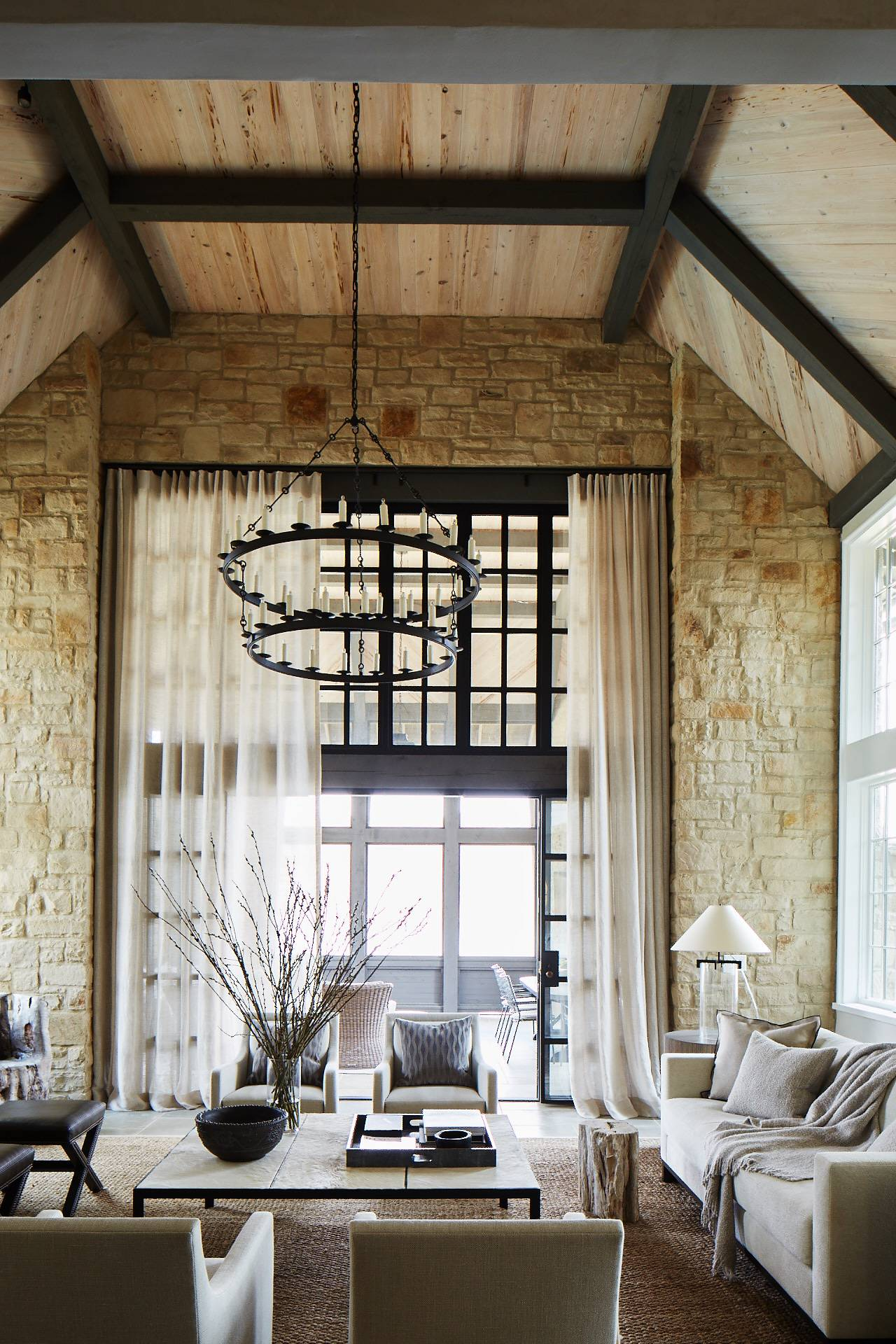 Stunning rustic luxe design in a living room with stone walls, ring style chandeliers, and wood plank ceilings - Jeffrey Dungan.