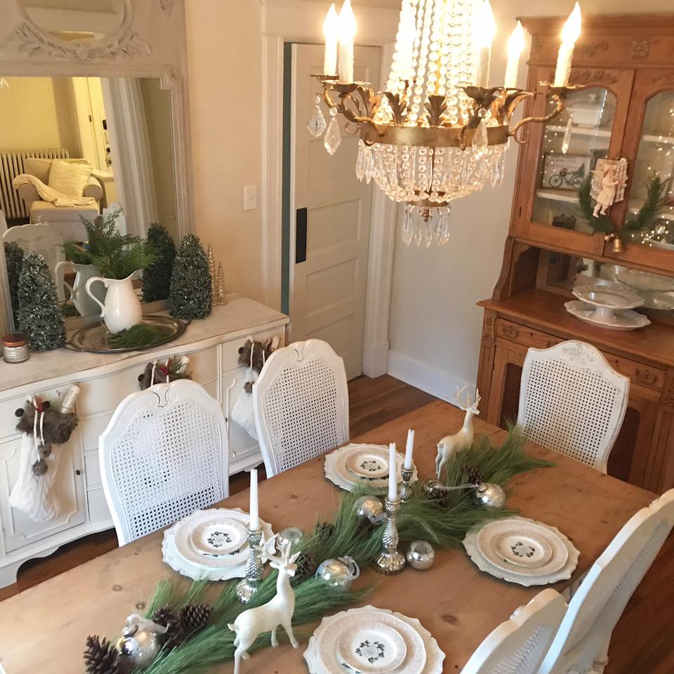 Farmhouse dining room with white shabby chic decor decorated simply for Christmas with greenery, silver balls, and neutral colors. #christmasdecor #diningroom #farmhousedecor #shabbychic
