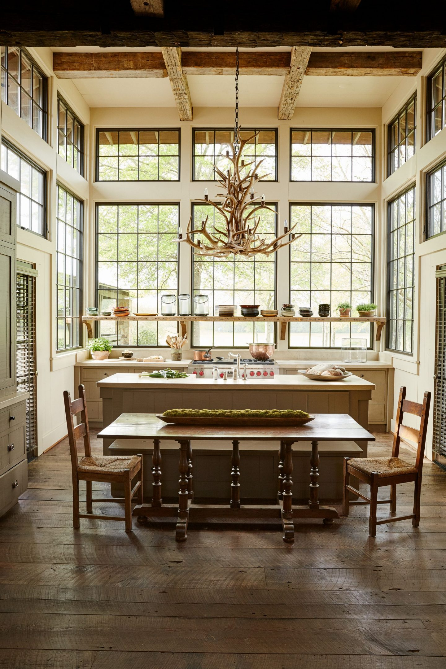 Magnificent walls of windows in a breathtaking rustic luxe kitchen designed by architect Jeffrey Dungan!
