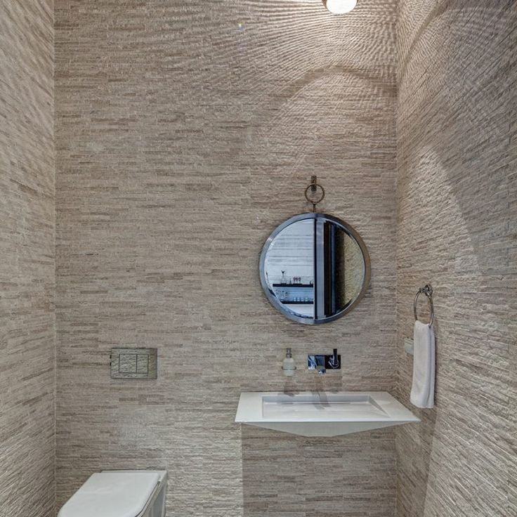 Powder room with walls tiled floor to ceiling with stone. Beautiful interior design inspiration from Chicago designer Cari Giannoulias on Hello Lovely Studio. #hellolovelystudio #interiordesign #carigiannoulias #chicagodesigner #interiordesigner #sophisticateddecor #understated #luxurydecor