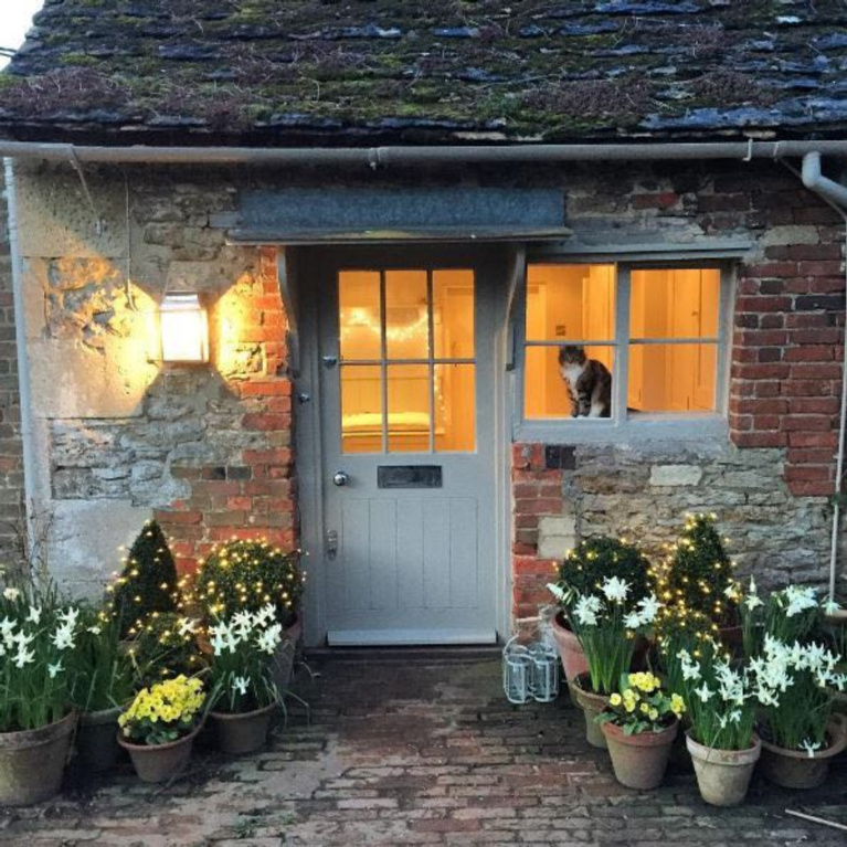 Charming English country cottage with wisteria and weathered brick for a storybook exterior! #Englishcountry #Englishcottage #wisteria #cottageexterior #stonecottage #storybook #houseexterior
