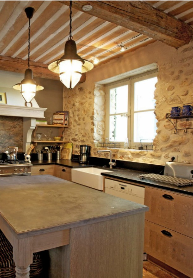 French farmhouse kitchen with rustic stone wall, coastal style pendants, and professional appliances. Provence French country kitchen from a vacation property offered by Haven In..