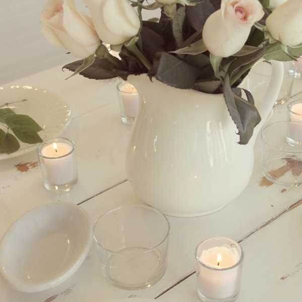 White farmhouse tablescape with ironstone, blush roses, and candlelight. Hello Lovely Studio.