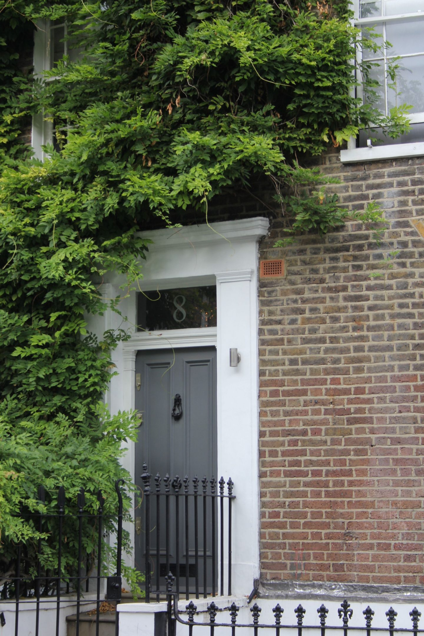 Charming grey door on row house. Hello Lovely Studio. Come tour these gorgeous front doors in Notting Hill and Holland Park...certainly lovely indeed. Curb appeal and Paint Color Inspiration. Lovely London Doors & Paint Color Ideas!