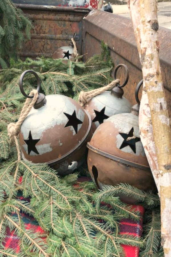 Large Farmhouse rustic Christmas bells and greenery in the back of a pickup at Urban Farmgirl in Rockford, IL. Hello Lovely Studio.