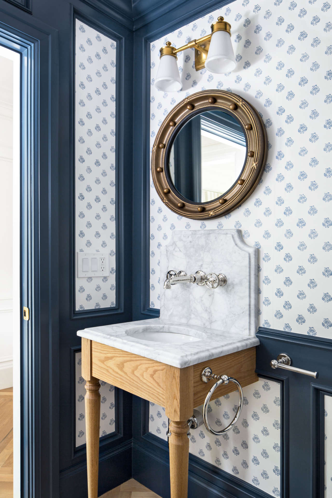 Traditional powder room with wood console sink with marble top,  blue and white wallpaper and navy blue trim. The Fox Group. Come explore these timeless design ideas...hello lovely indeed.#powderroom #traditional #thefoxgroup