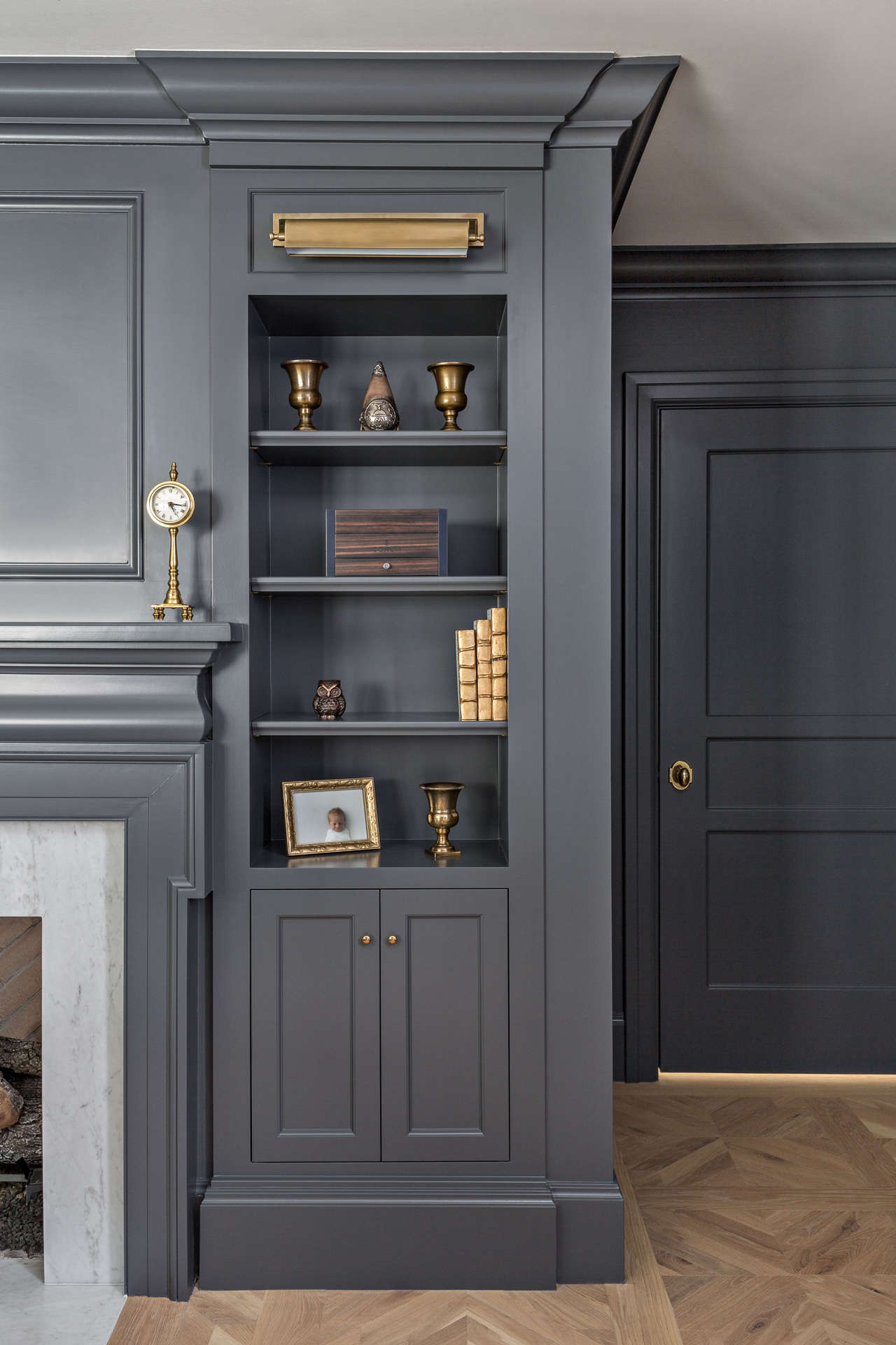 Dark gray painted built in cabinets flank a fireplace in a renovated Tudor home's den. Come explore these timeless design ideas...hello lovely indeed. #thefoxgroup #builtins #bluegray #darkgraytrim #livingrooms ##interiordesign