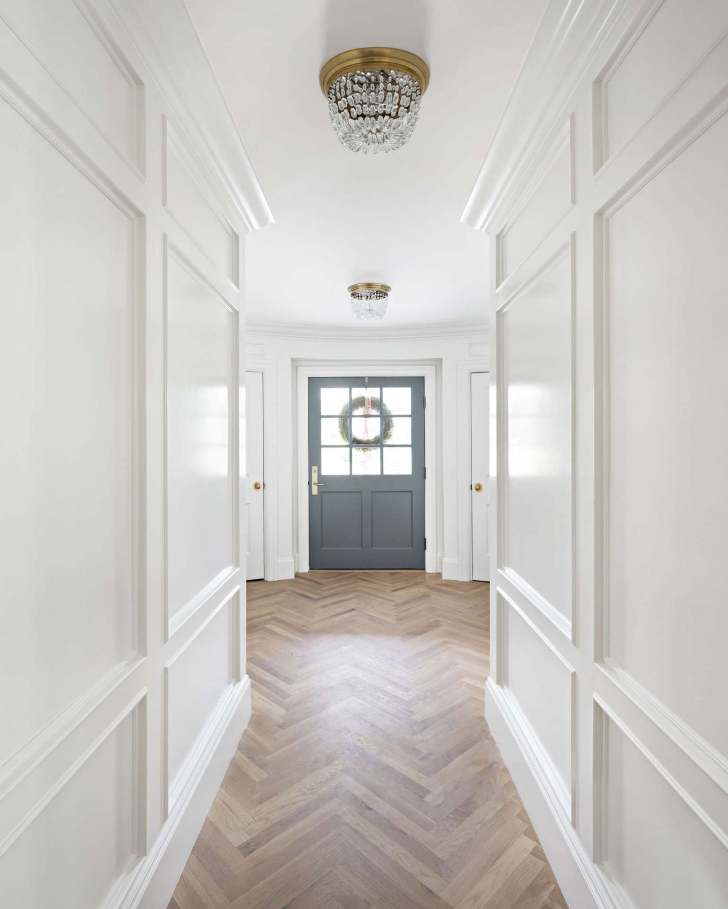 Herringbone flooring and beautiful paneled walls painted Benjamin Moore Simply White in a Tudor home's entry. The Fox Group. Come explore these timeless design ideas...hello lovely indeed. #benjaminmooresimplywhite #interiordesign #thefoxgroup