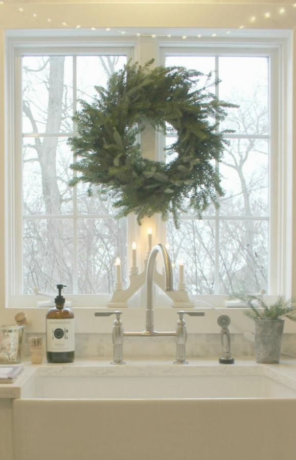 My Christmas kitchen with Scandinavian style and a fresh wreath over farm sink - Hello Lovely Studio.