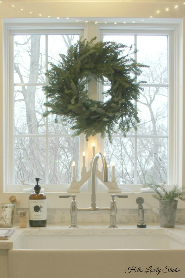 White Christmas decor inspiration from a simple kitchen sink with fresh wreath. Hello Lovely Studio.