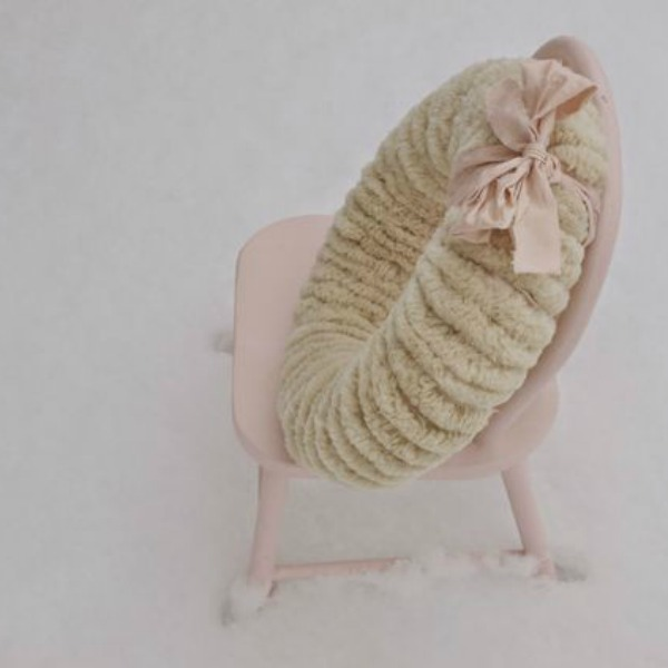 Wooly pom pom wreath on a wee pink chair in the snow by Hello Lovely Studio.