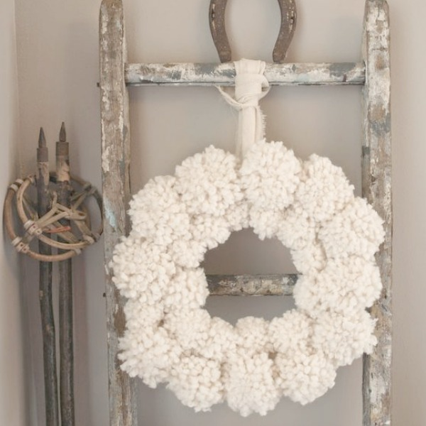 My pom pom wreath on a chippy ladder with vintage european ski poles and horseshoe. #hellolovelystudio