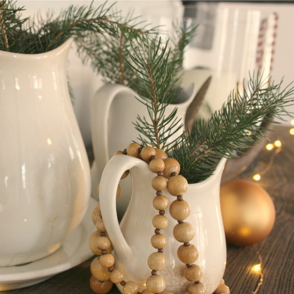 White ironstone pitchers with fresh evergreen sprigs for a farmhouse Christmas decor look by Hello Lovely Studio.