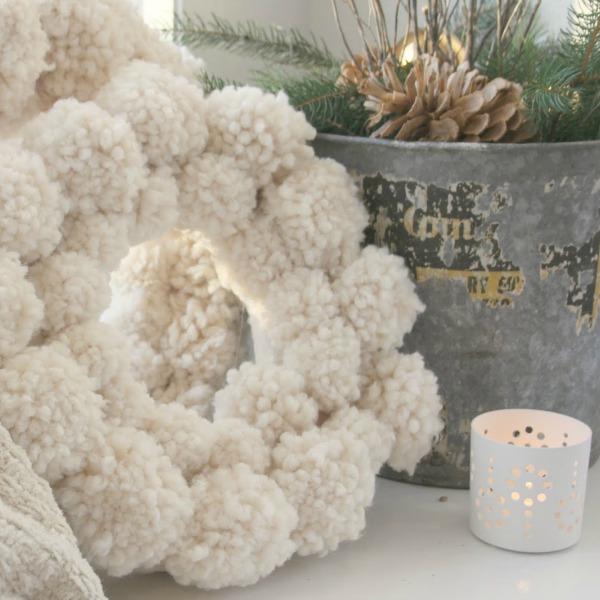 A fuzzy wuzzy wooly ivory handmade pom pom wreath is perfect for a cozy white Christmas! Hello Lovely Studio. #christmasdecor #christmaswreath #pompom #handmade