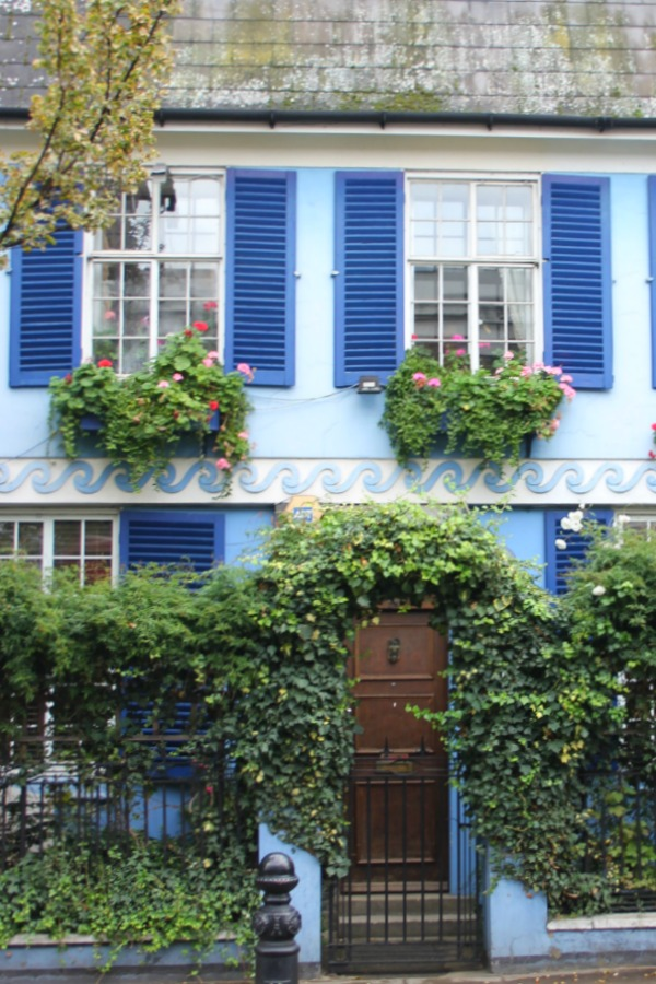 Charming European cottage with royal blue shutters on bright sky blue house exterior with window boxes. Hello Lovely Studio. Notthing Hill home.