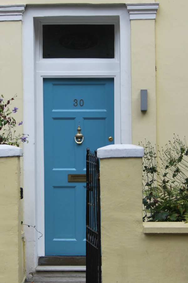 French blue painted front door of a yellow row house. Hello Lovely Studio. Come tour these gorgeous front doors in Notting Hill and Holland Park...certainly lovely indeed. Curb appeal and Paint Color Inspiration. Lovely London Doors & Paint Color Ideas!