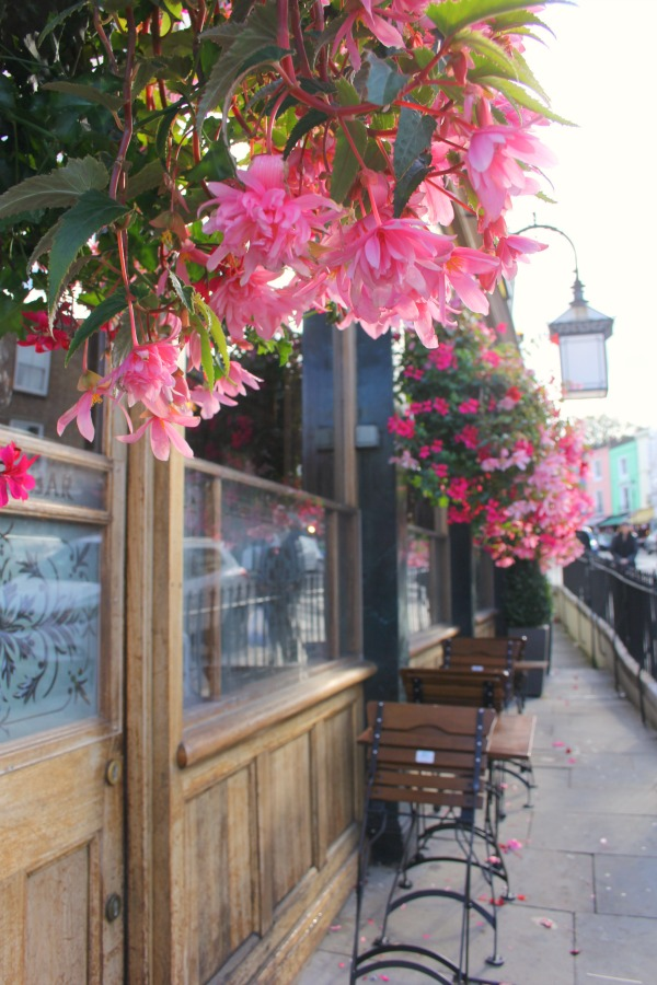Vibrant cascading pink flowers on an English pub exterior in London by Hello Lovely Studio.