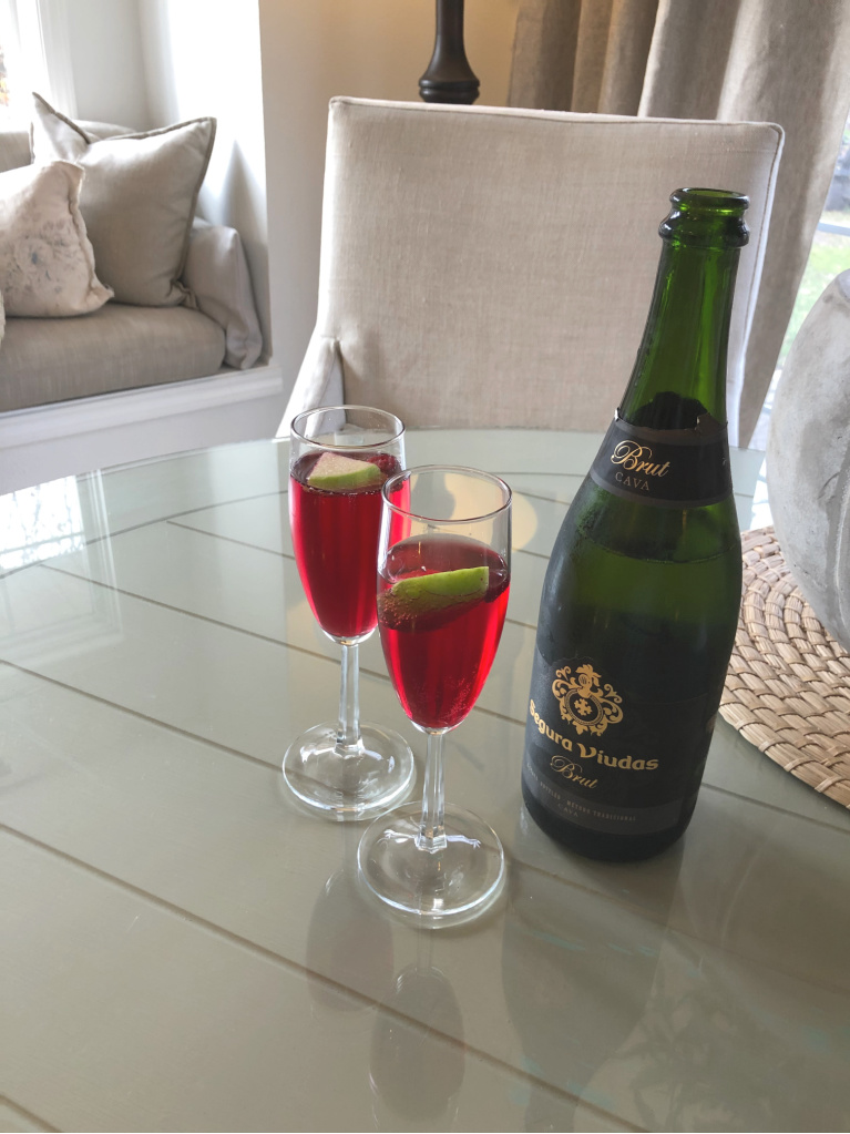 Simple champagne cocktail idea with green apple and fresh cranberry - Hello Lovely Studio.