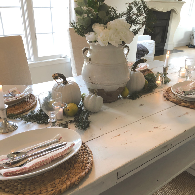 Simple Thanksgiving tablescape with white farm table, pale pumpkins, fresh greenery and candlelight - Hello Lovely Studio.
