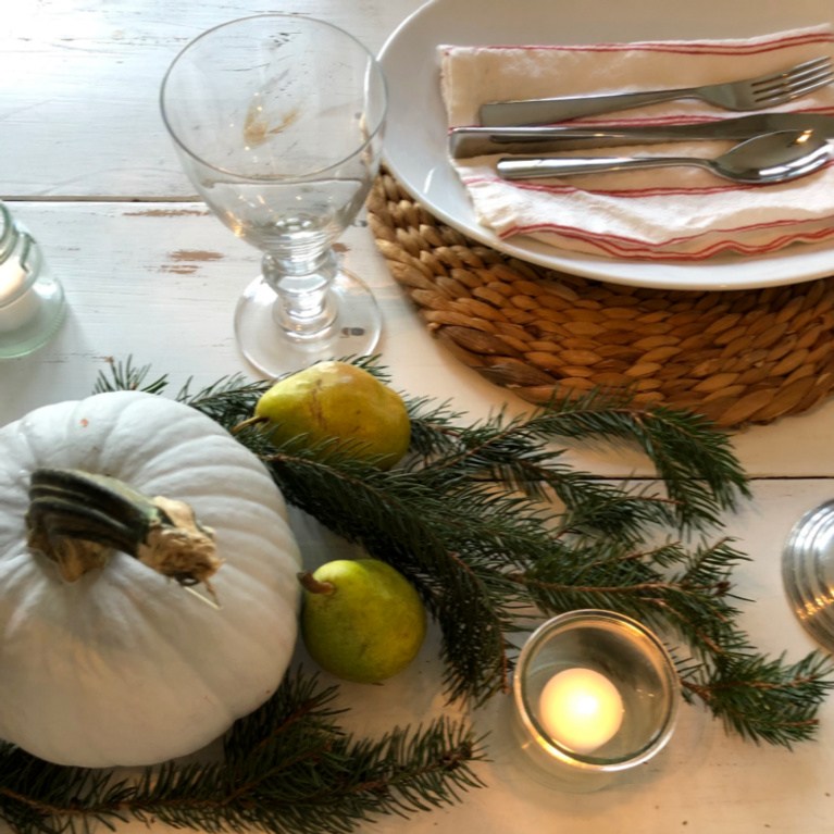 Simple Thanksgiving tablescape with white farm table, pears, pale pumpkins, fresh greenery and candlelight - Hello Lovely Studio.