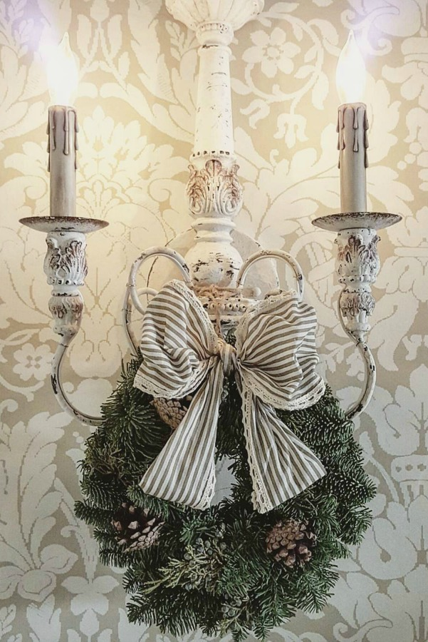 French country sconce with Christmas wreath and striped ribbon. #frenchcountry #christmasdecor #elegantdecor