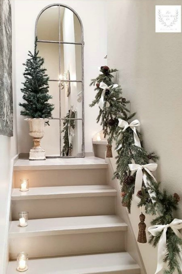 White Christmas decor in a French country home with minimal simple beauty on a staircase with fresh greenery, white bows, and pale decor. Beautiful holiday decor inspiration from interior designers and bloggers. Come discover 28 Amazing Christmas Decorating Ideas! #christmasdecor #holidaydecorating