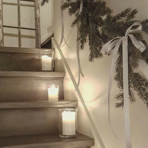 Simple glass hurricanes and whtie candles line a staircase with fresh greenery garland in a French inspired home. #christmasdecor #simplechristmas #frenchcountry #frenchnordic