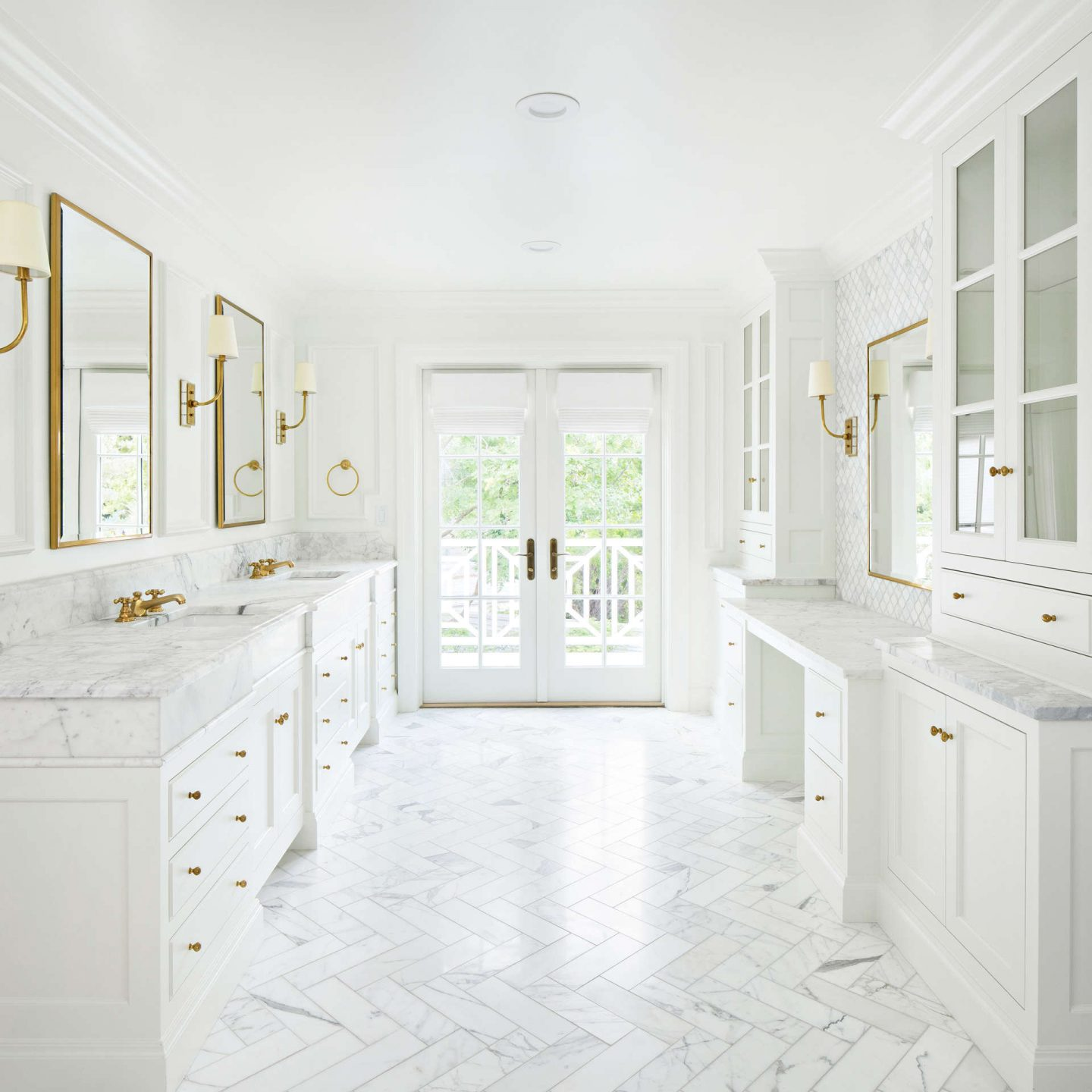 Calcatta marble is set in a herringbone pattern on the floor of a luxurious bathroom. #thefoxgroup #bathroomdesign #calacattamarble #herringbone