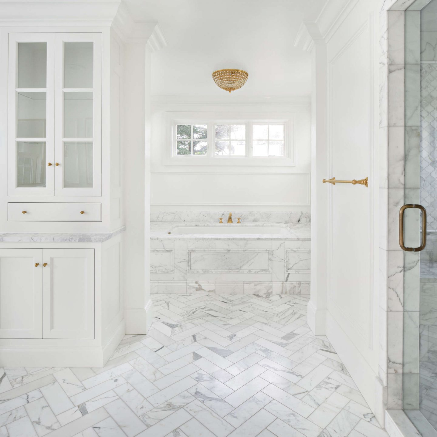 Calacatta marble tile and tub surround in a luxurious white classic bathroom. Come explore these timeless design ideas...hello lovely indeed.  #thefoxgroup #bathroomdesign #calacattamarble