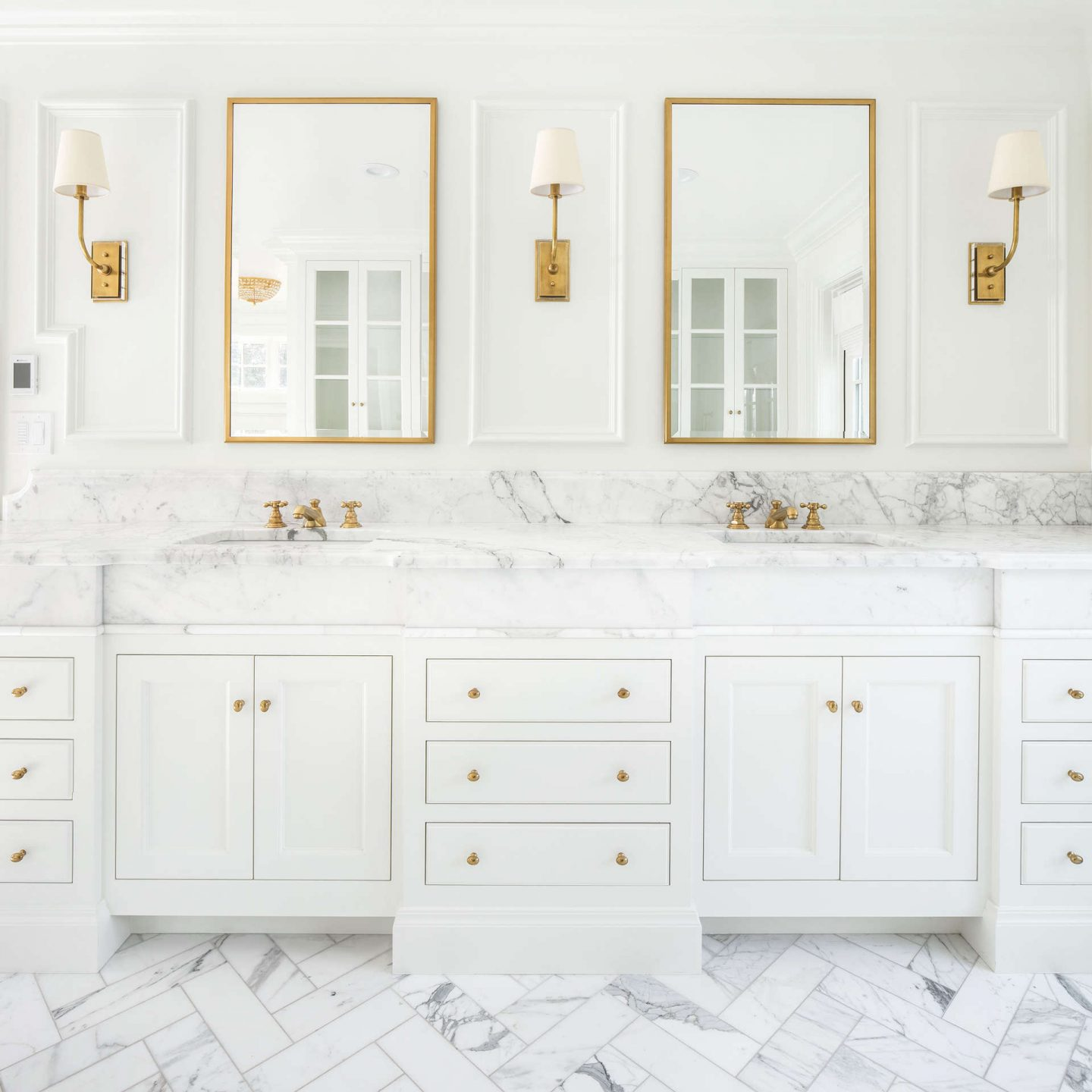 Double vanities in a white classic bathroom with Calacatta marble and brass hardware. #thefoxgroup #bathroom #brasshardware #calacatta