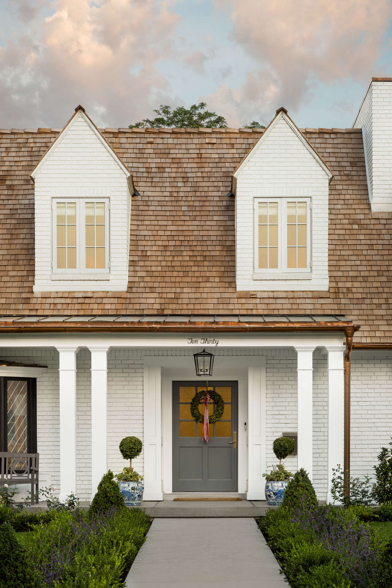 Exterior of a beautiful white brick Tudor home with grey door with wreath. #thefoxgroup #houseexterior #tudor #whitebrick